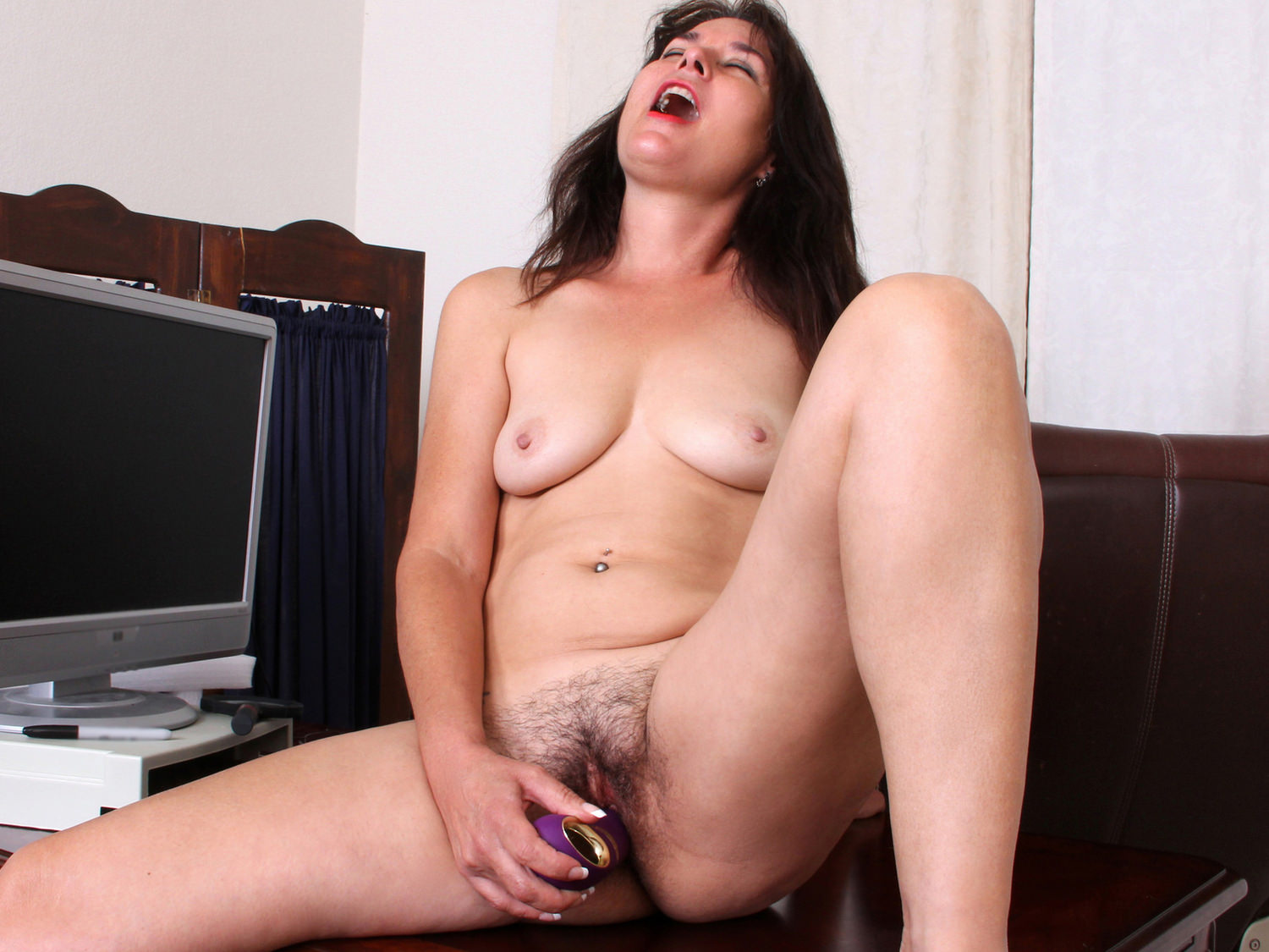 Hairy mom is masturbating on the couch while a hidden camera is recording her in action